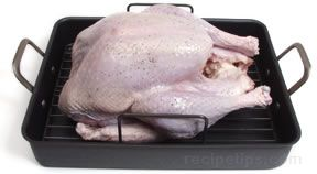 place the turkey breast side up on a cooking rack in a shallow roasting pan and place the pan in the center of the lowest rack of a preheated oven